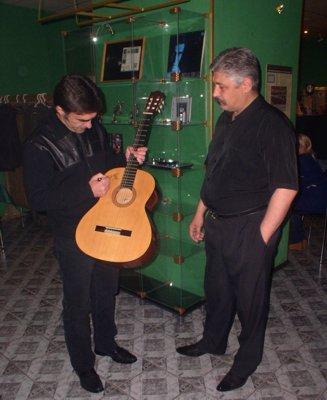 Бутусов ставит автограф на гитаре